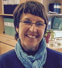Porträtt Christina Forsberg med kort hår och glasögon.