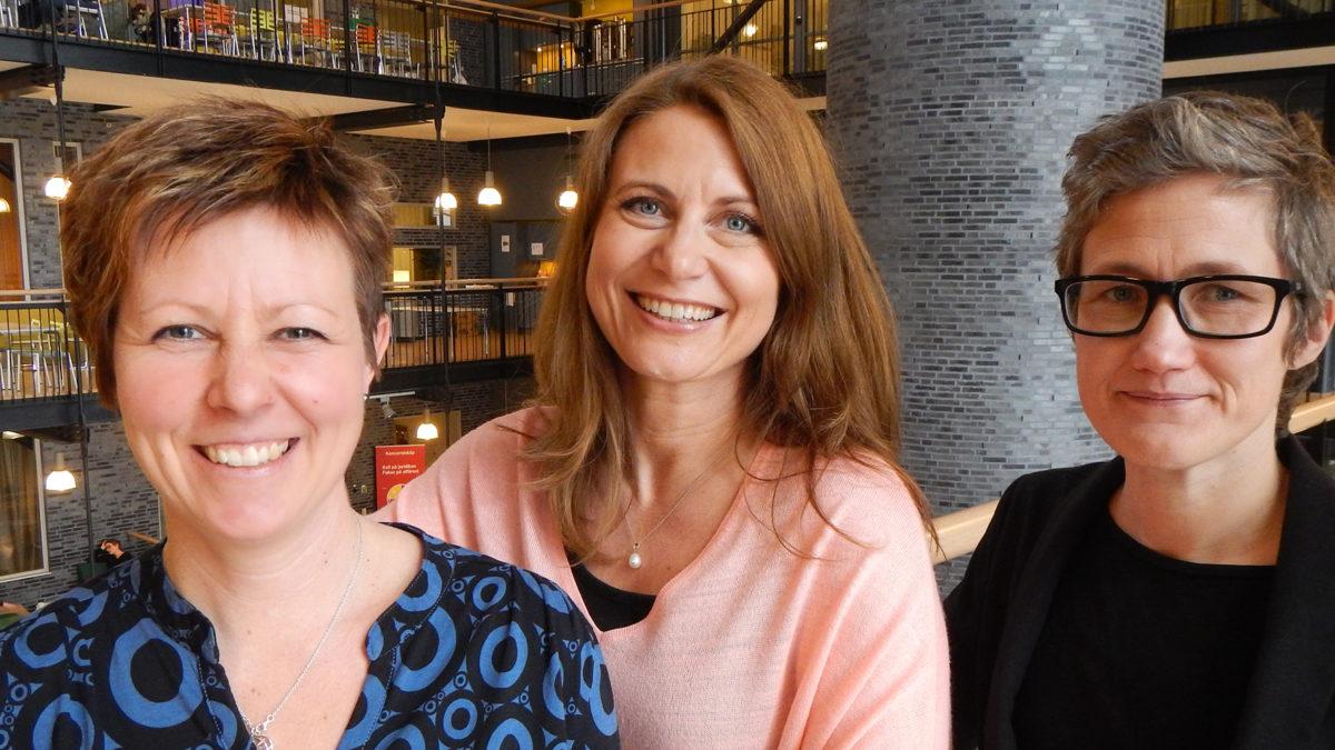 Grupporträttbild tre leende medarbetare