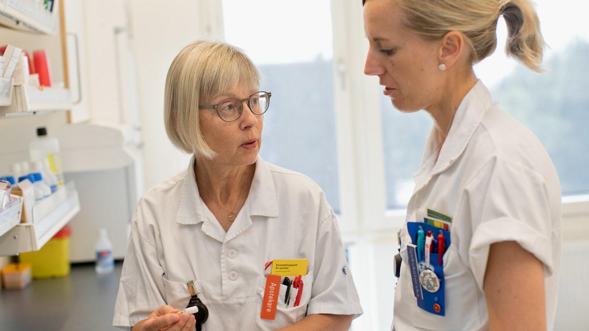 bild på apotekare i vården som visar kollega något