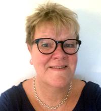 Porträtt Helen Eriksson med kortklippt ljust hår och glasögon