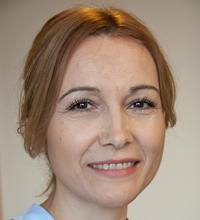 Ansiktsporträtt Zehra Kozica med uppsatt brunt hår