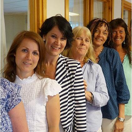Sju glada medarbetare varav sex kvinnor, på rad i korridor