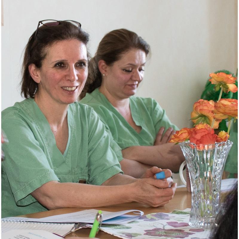 Två kvinnor, medarbetare på demensboende, i gröna arbetsskjortor sitter vid bord