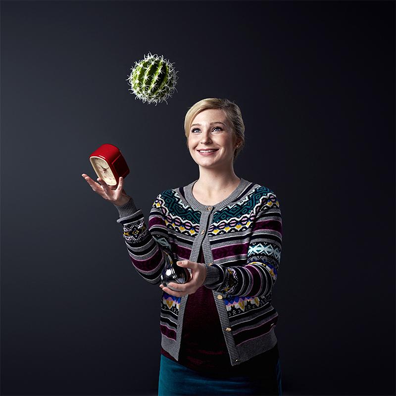En kvinna ler och jonglerar med lätthet en kaktus, en väckarklocka och ett bouleklot.