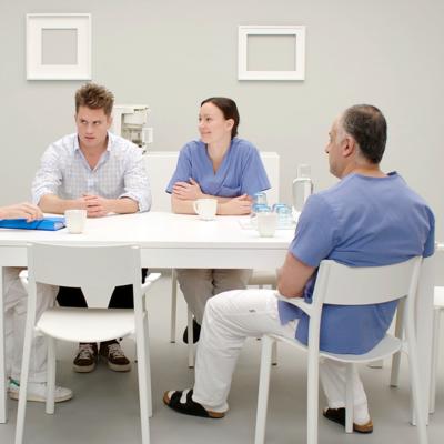 Sjukvårdspersonal sitter runt ett bord och samtalar
