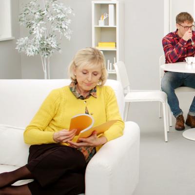En person i gul kofta sitter i en vit soffa och läser en bok