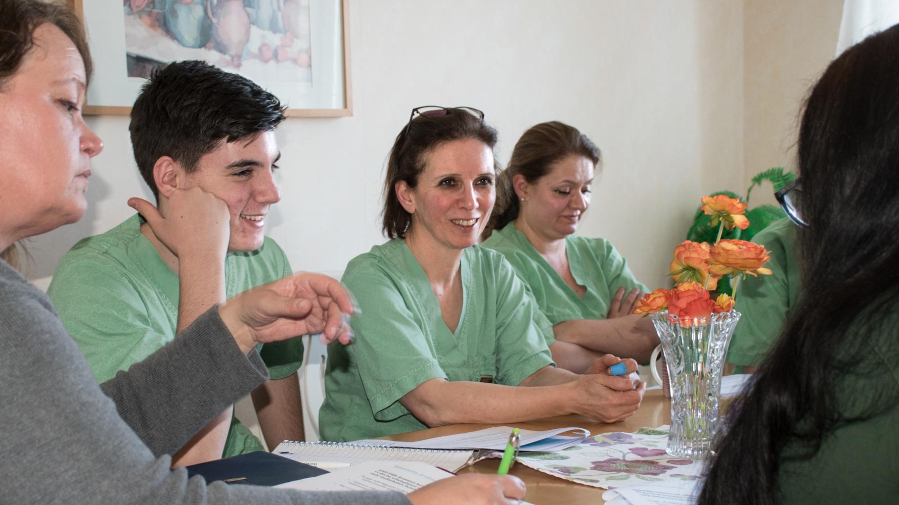 Vårdpersonal sitter runt ett bord och samtalar vid arbetsplatsträff