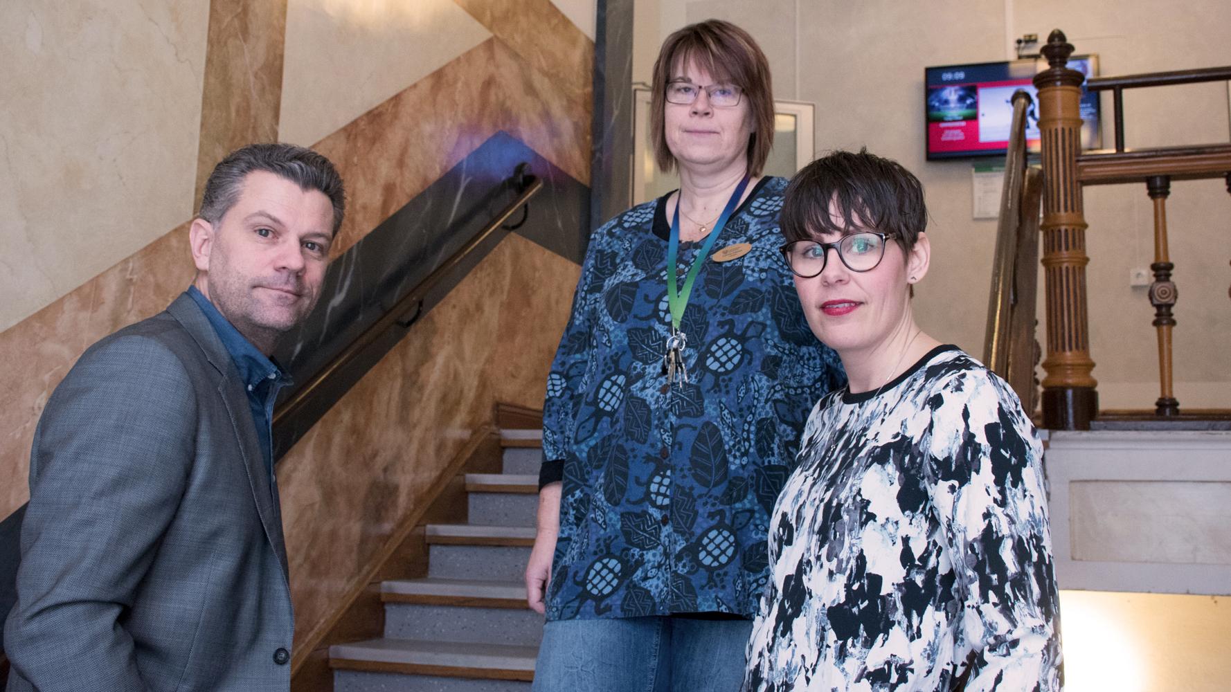 Rektor och två lärare stående i trappa