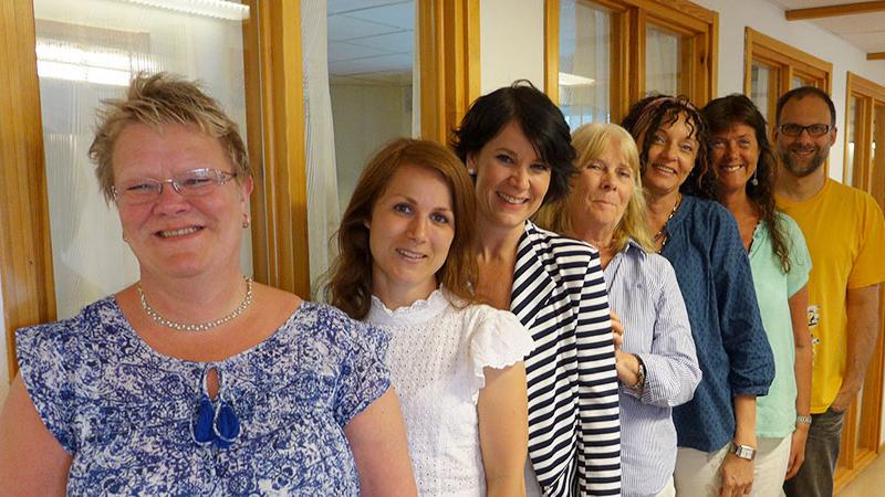 Bild på sju leende medarbetare som står på rad i en korridor