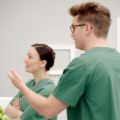 Två personer i gröna arbetskläder står vid ett schema och diskuterar livligt