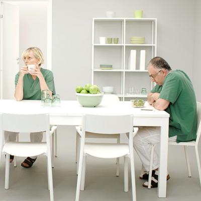 Två personer i gröna arbetskläder sitter vid ett lunchbord och den ena ser ledsen ut