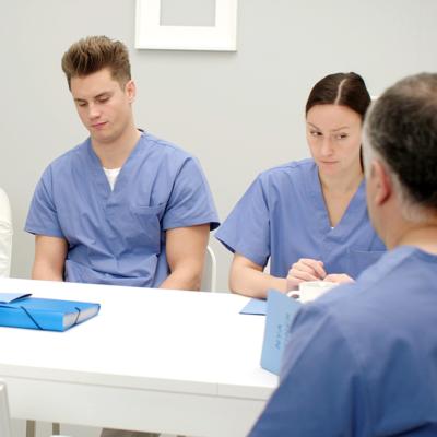 Sjukvårdspersonal sitter vid ett bord och är arga på varandra
