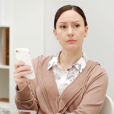 En kvinna håller i en mobiltelefon och tittar bekymrat upp